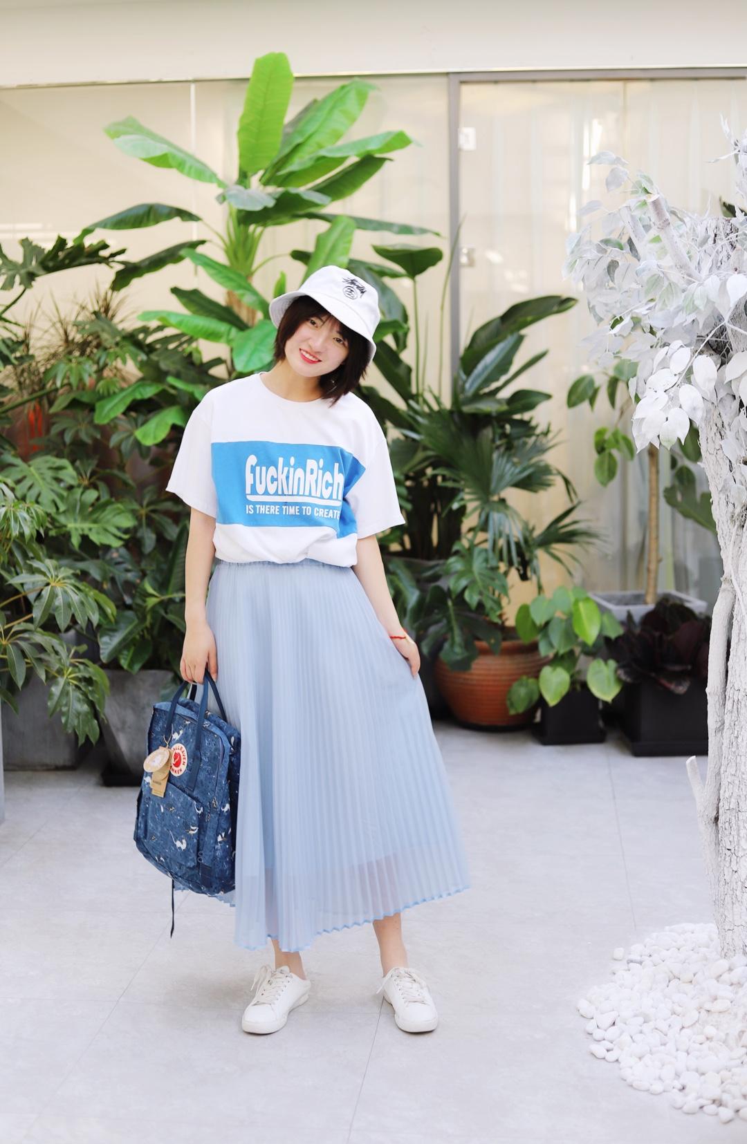 上身是一件白色蓝色印花短袖 下身是一条蓝色百褶裙 搭配一双白色帆布鞋 戴上一顶白色的渔夫帽 拎上一个蓝色的书包 这样一身颜色就很好看啦 #夏天就要做个甜到冒泡girl#