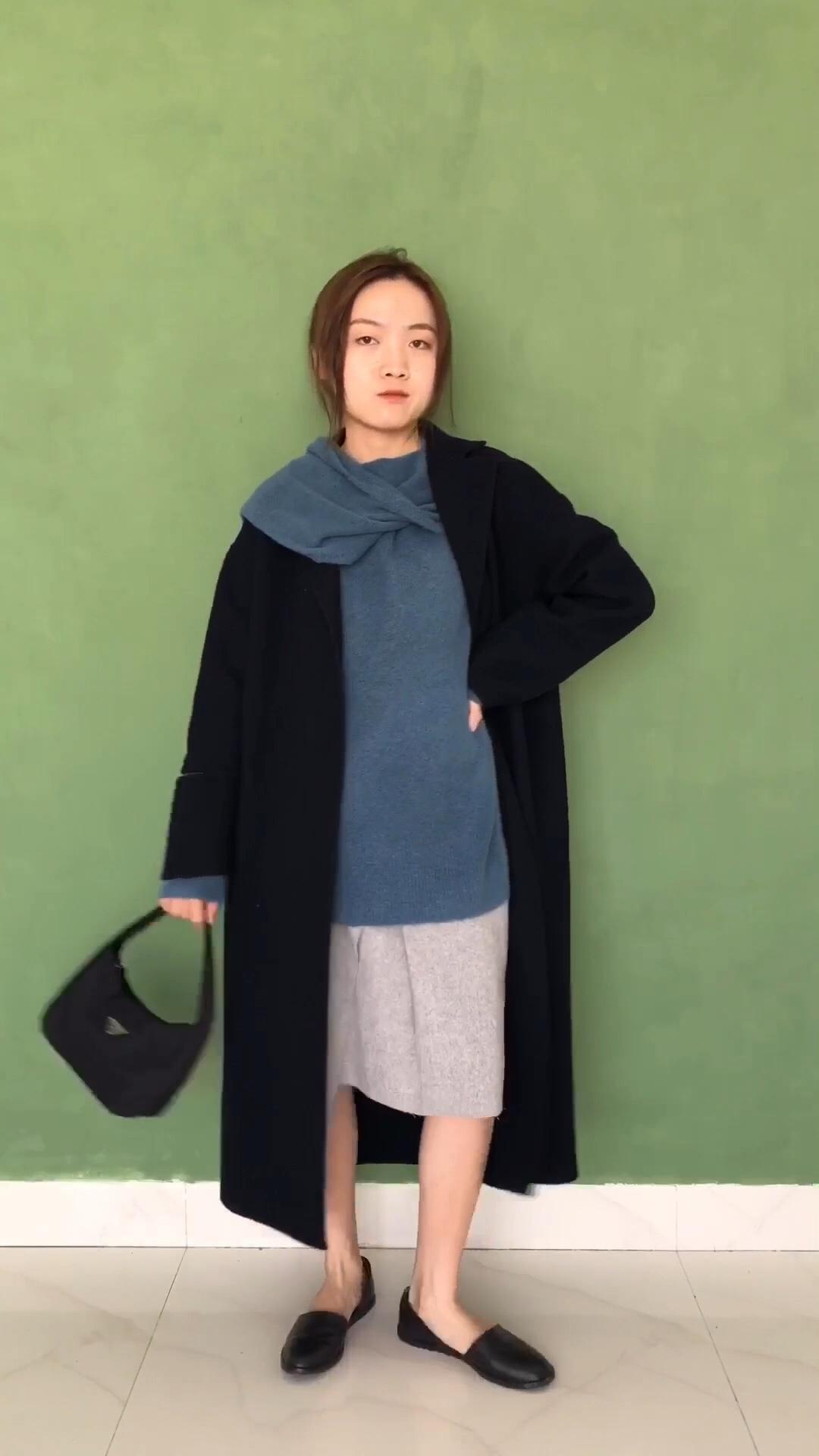 """内搭蓝色的毛衣+灰色的半裙,这个颜色组合太油温啦,越看越喜欢💕毛衣跟围巾是连接在一起的,随意的捏造造型都很好看,半身裙前面是两片不规则设计,有镭射切割边出来的不规则抽丝效果~最外面再穿一件黑色毛呢大衣,看起来是不是更显瘦啦~喜欢它袖口小开口的设计~不经意间透露的小心机😁 #双11梨形身材如何""""瘦""""十斤?#"""